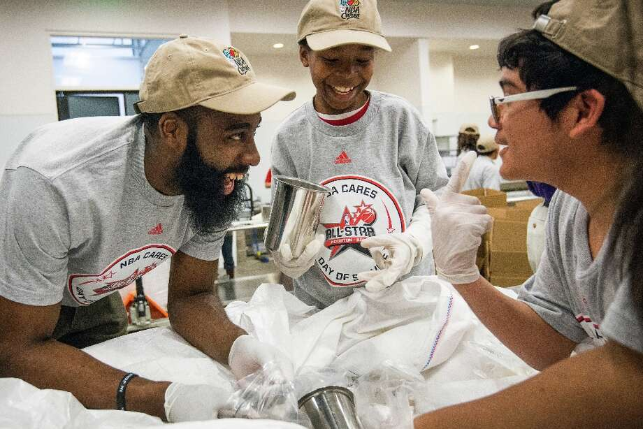 Rockets shooting guard James Harden laughs with students from KIPP Liberation College Prep as he helps sort and package food for needy Houstonians during an NBA Cares All-Star Day of Service project at the Houston Food Bank on Friday. Photo: Smiley N. Pool / © 2013  Houston Chronicle