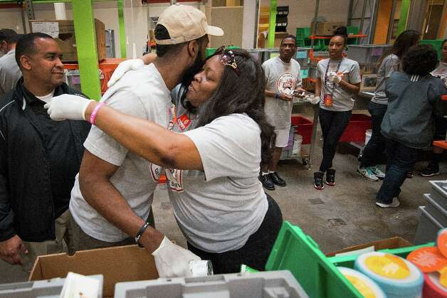 Houston Rockets shooting guard James Harden gets a hug from his mother Monja Willis as they help sort and package food for needy Houstonians. Photo: Smiley N. Pool / © 2013  Houston Chronicle