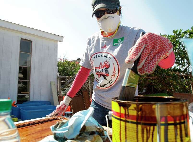 Lesile Nguyen of Houston works to stain cabinets outside a home in the Foster Place Community as par