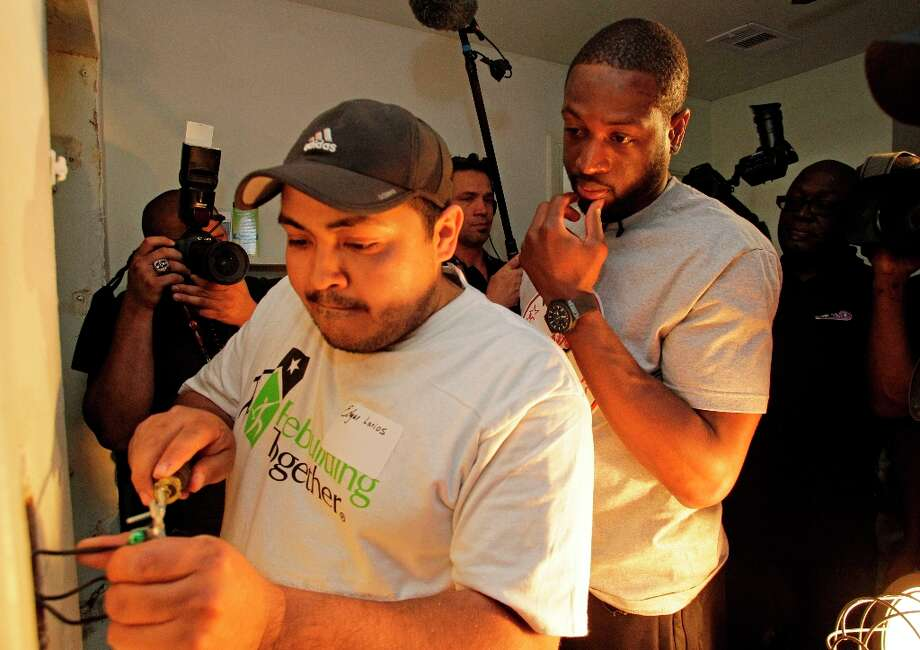 NBA player Dwyane Wade, right, watches as electrician Edgar Larios, left, works on a light switch inside the Foster Place Community home of Myrteal Gray. Photo: Melissa Phillip / © 2013 Houston Chronicle