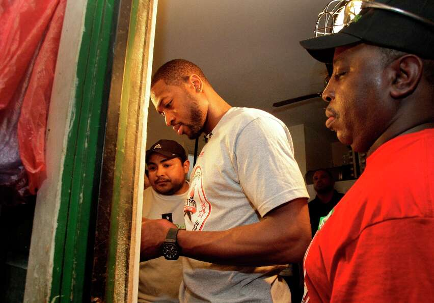 With the help of electrician Edgar Larios, left, NBA player Dwyane Wade, center, works on a light sw
