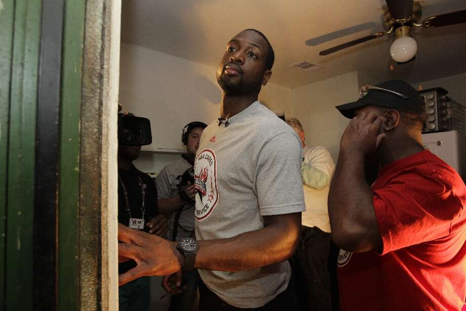 NBA player Dwyane Wade , left, works on a light switch with volunteer Edward Price, shown right, inside the Foster Place Community home of Myrteal Gray. Photo: Melissa Phillip / © 2013 Houston Chronicle