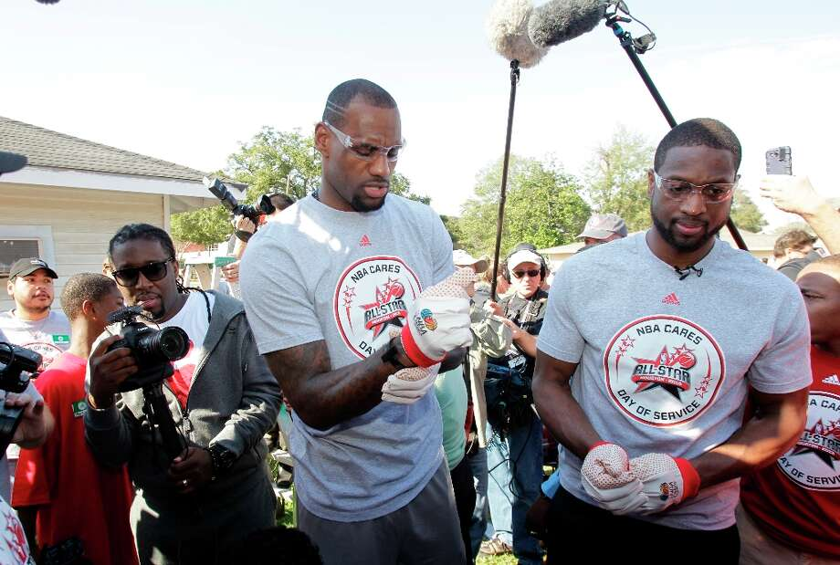 NBA players LeBron James, left, and Dwyane Wade, center, talk outside the Foster Place Community home of  Myrteal Gray. Photo: Melissa Phillip / © 2013 Houston Chronicle
