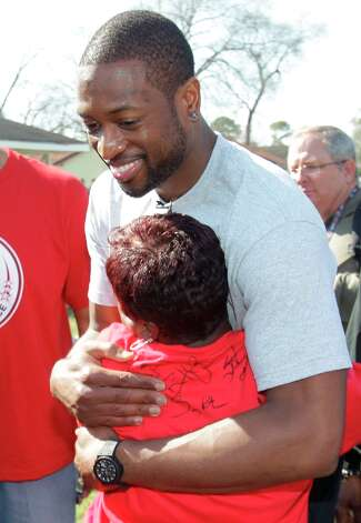 NBA player Dwyane Wade hugs homeowner Myrteal Gray outside her Foster Place Community home. Photo: Melissa Phillip / © 2013 Houston Chronicle