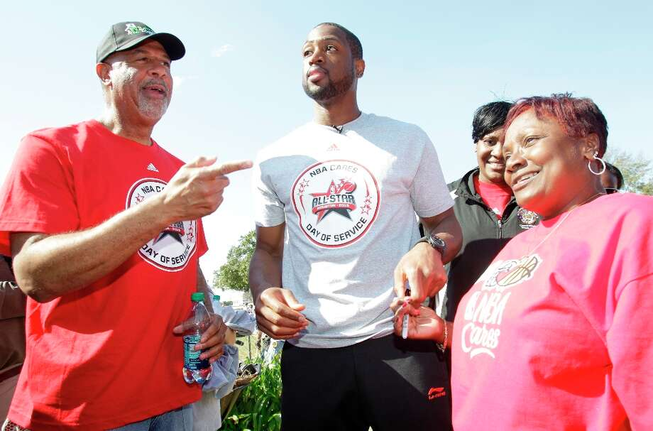 Skip Robinson, left, and NBA players Dwyane Wade, center, talk with homeowner Myrteal Gray, right, outside her Foster Place Community home. Photo: Melissa Phillip / © 2013 Houston Chronicle