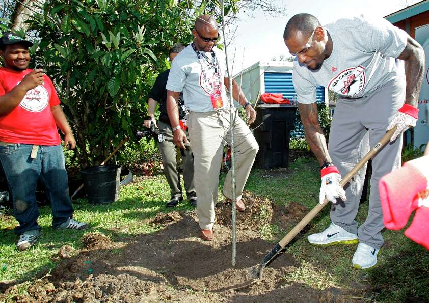 NBA player LeBron James, right, helps plant a tree outside the Foster Place Community home of Myrtea
