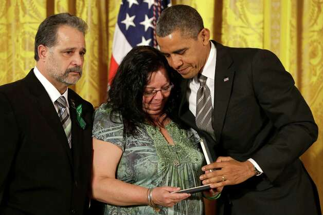 President Barack Obama presents a 2012 Citizens Medal to the parents of slain Sandy Hook Elementary School teacher Victoria Soto, Donna and Carlos Soto,  Friday, Feb. 15, 2013, during a ceremony in the East Room of the White House, in Washington. Photo: Jacquelyn Martin, Associated Press/Jacquelyn Marti / Associated Press
