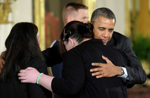 President Barack Obama hugs the family of Rachel Davino, 29, who was a behavioral therapist at Sandy Hook Elementary, before presenting her posthumously with the 2012 Presidential Citizens Medal, the nationís second-highest civilian honor, during a ceremony in the East Room of the White House in Washington, Friday, Feb. 15, 2013. Mary Davino, mother, is at left, and sister Sarah Davino, is at right. Photo: Susan Walsh, AP Photo/Susan Walsh / AP2013 Associated Press