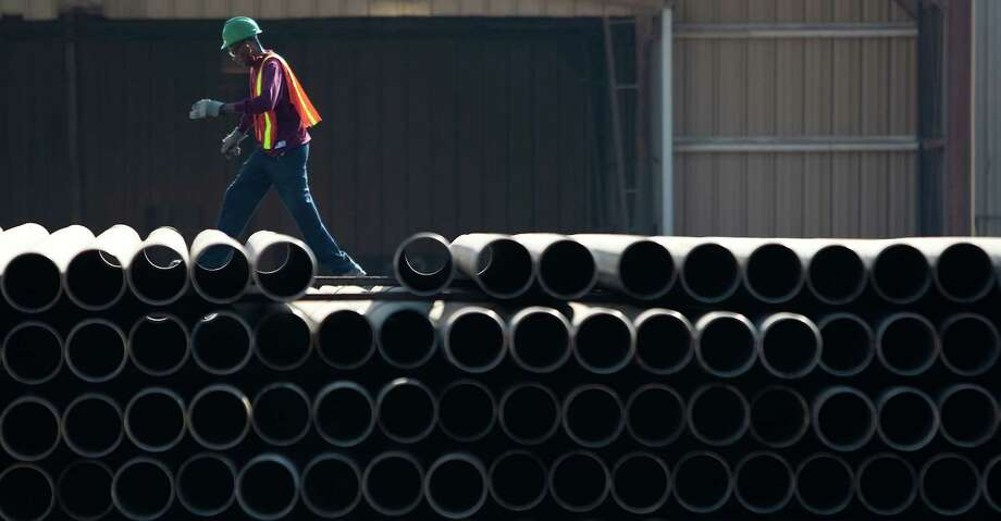 A Tenaris employee lines up a stack of pipes at the company's facility in Conroe. The international company, which also has operations in Houston, said Friday it will add a $1.5 billion plant in Matagorda County to produce piping for shale drilling. Photo: Nick De La Torre, Staff / Houston Chronicle