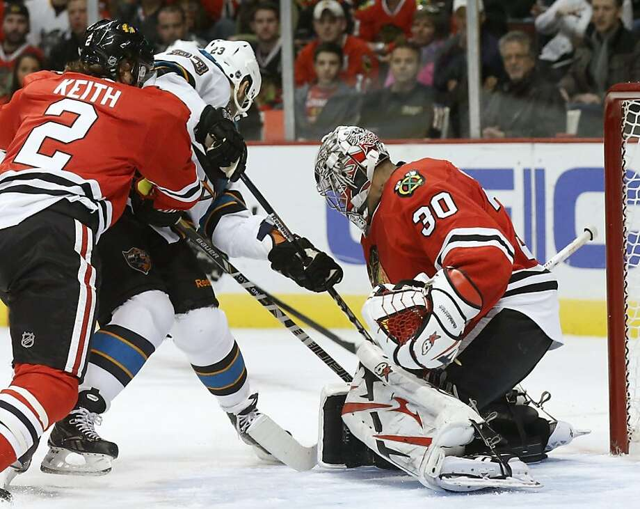 Chicago Blackhawks goalie Ray Emery (30) saves a rebound attempt by San Jose Sharks center Scott Gomez (23) as Duncan Keith (2) also defends during the first period of an NHL hockey game Friday, Feb. 15, 2013, in Chicago. (AP Photo/Charles Rex Arbogast) Photo: Charles Rex Arbogast, Associated Press