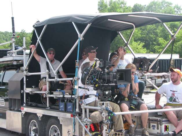 "A film crew is seen on the back of a camera truck after a take during filming of a scene with Ryan Gosling in ""The Place Beyond the Pines."" The movie was being filmed Thursday on Route 5 in Glenville. (Desiree LaBombard / Special to the Times Union)"