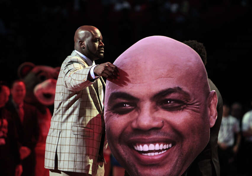 Shaquille O'Neal grabs a cutout of Charles Barkley.