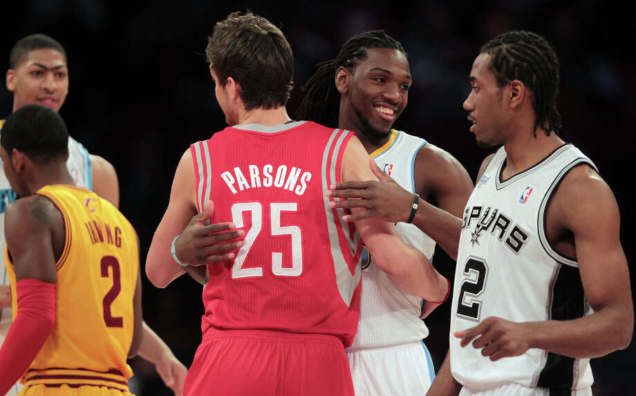 Team Shaq forward Chandler Parsons of the Rockets hugs Kenneth Faried of the Nuggets as they take the court. Photo: James Nielsen, Chronicle / © Houston Chronicle 2013