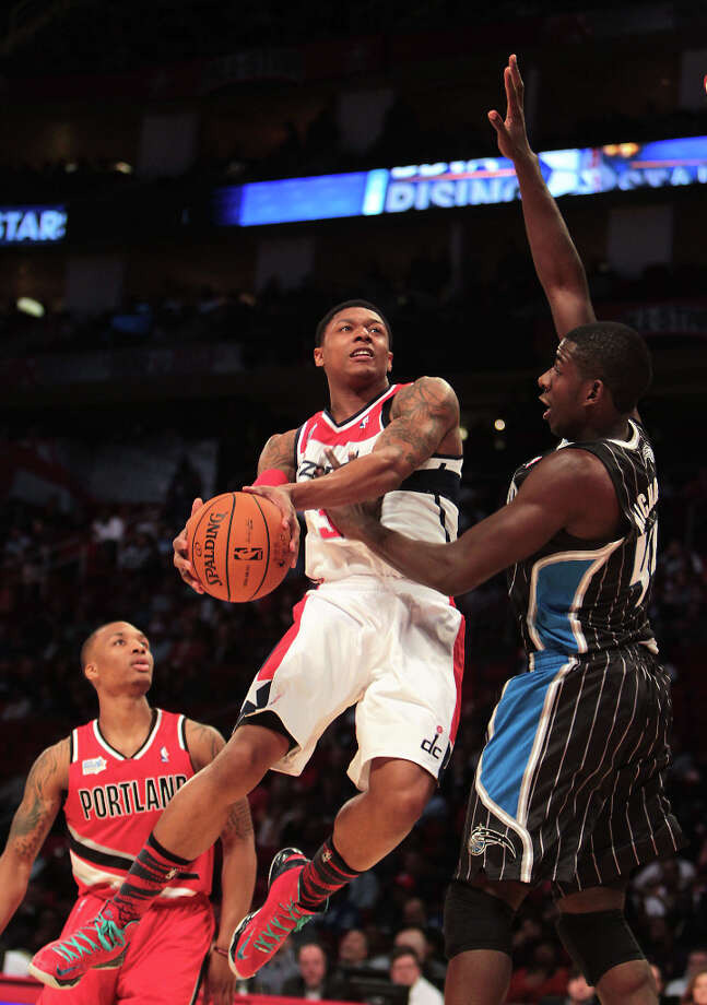 Bradley Beal of the Wizards goes to the basket as Andrew Nicholson of the Magic defends. Photo: James Nielsen, Chronicle / © Houston Chronicle 2013