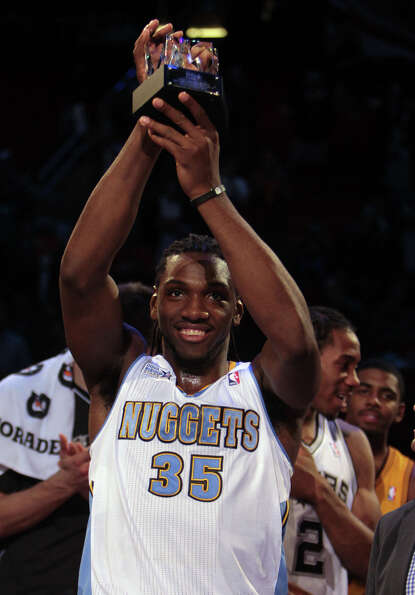 Kenneth Faried of the Nuggets lifts up his MVP trophy.