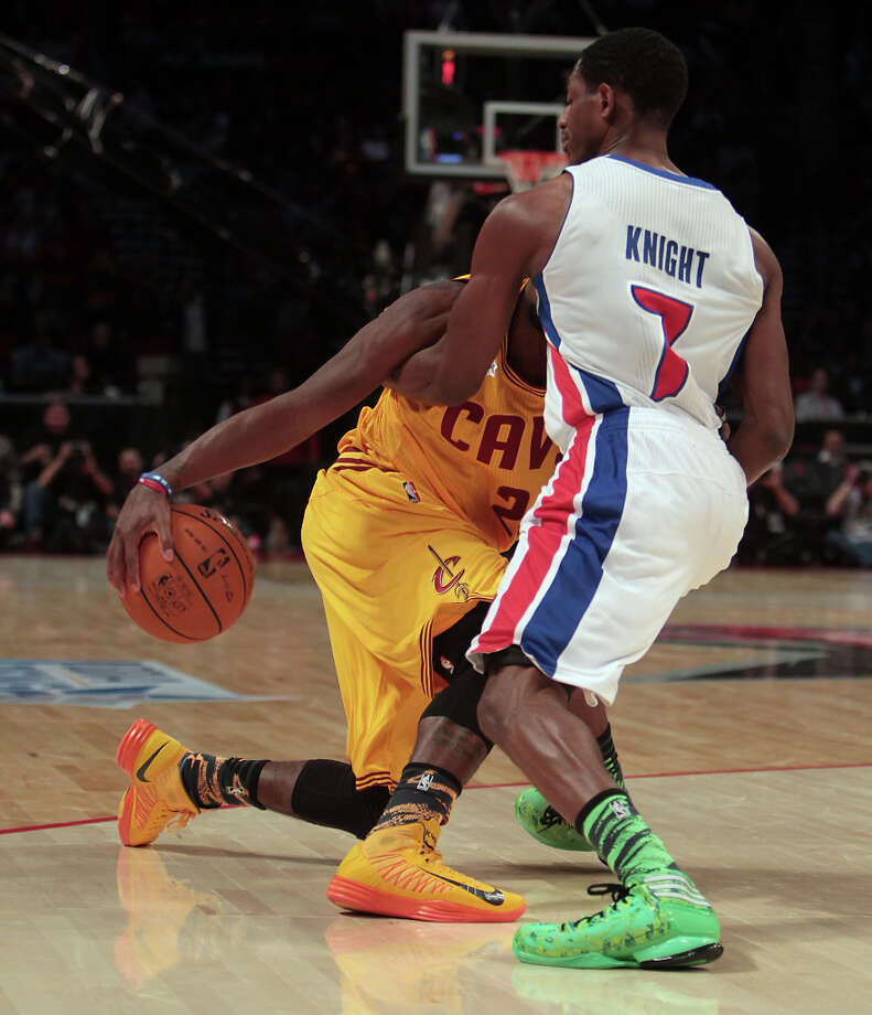 Kyrie Irving of the Cavaliers is tied up by Brandon Knight of the Pistons. Photo: James Nielsen, Chronicle / © Houston Chronicle 2013