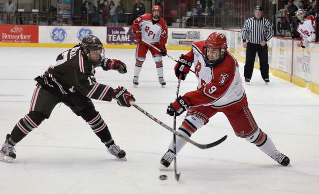 RPI's #9 Matt Neal gets a shot past  Brown's #17 Marc Senecal, left, during Friday night's game at the Houston Field House in Troy  Feb. 15, 2013.  (John Carl D'Annibale / Times Union) Photo: John Carl D'Annibale / 00021137A