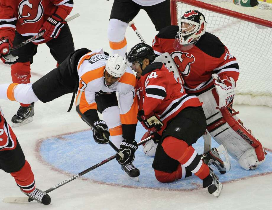 New Jersey Devils' Bryce Salvadore (24) checks Philadelphia Flyers' Wayne Simmonds (17) in front of Devils goaltender Martin Brodeur during the second period of an NHL hockey game Friday, Feb. 15, 2013, in Newark, N.J. (AP Photo/Bill Kostroun) Photo: Bill Kostroun