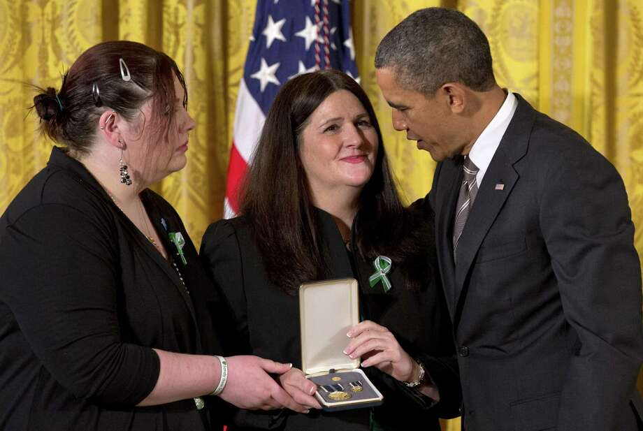 President Barack Obama presents the 2012 Presidential Citizens Medal to Mary D'Avino (center) and Sarah D'Avino, the mother and sister of slain teacher's aide Rachel D'Avino. Photo: Jacquelyn Martin / Associated Press