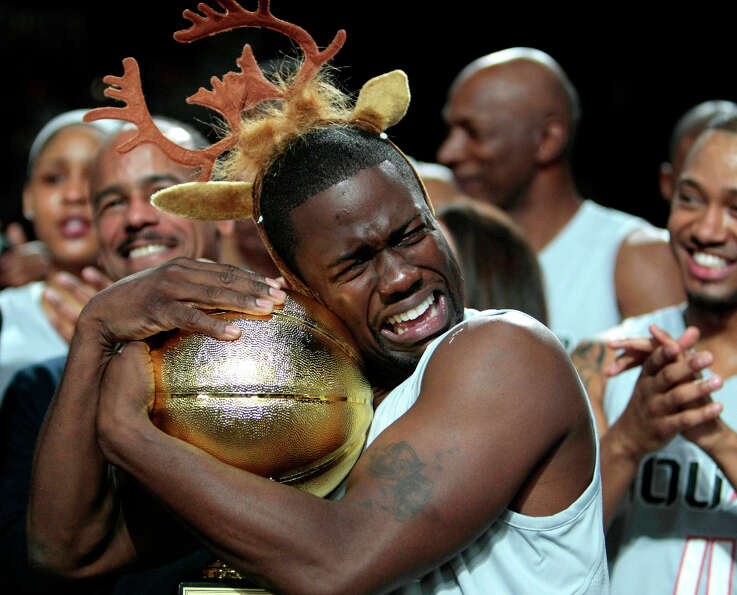 After being named MVP of the Celebrity game comedian Kevin Hart hugs the MVP trophy during the 2013