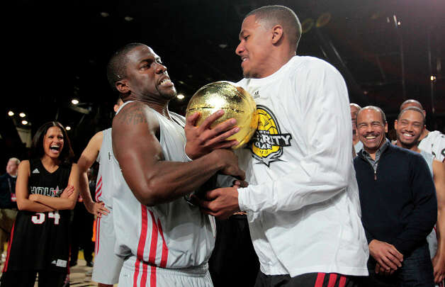 (l-r) After being named MVP of the Celebrity game comedian Kevin Hart fights actor Nick Cannon for the MVP trophy during the 2013 Sprint All-Star Celebrity game. Photo: Billy Smith II, Houston Chronicle / © 2013 Houston Chronicle