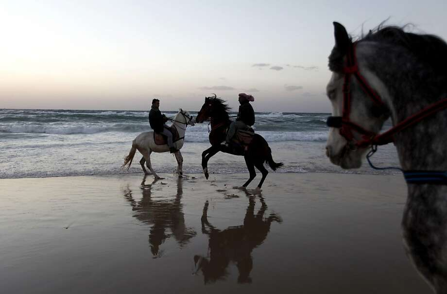 Palestinians ride horses on Gaza beach as the sun sets in Gaza City, Friday, Feb. 15, 2013.  Photo: Hatem Moussa, Associated Press