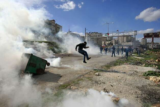 Palestinians are covered with tear gas smoke during clashes with Israeli troops, outside Ofer, an Israeli military prison near the West Bank city of Ramallah, Friday, Feb. 15, 2013. Palestinian demonstrators clashed with Israeli soldiers on Friday at a rally held in support of a prisoner observing an intermittent hunger strike to protest his incarceration. The Israeli military said about 200 Palestinians threw rocks at soldiers who responded with tear gas during the rally outside Ofer prison in the West Bank. The protesters called for the release of Samer Issawi, who has been on an on-again, off-again hunger strike for several months as he serves time for alleged terror activity.  Photo: Majdi Mohammed, Associated Press