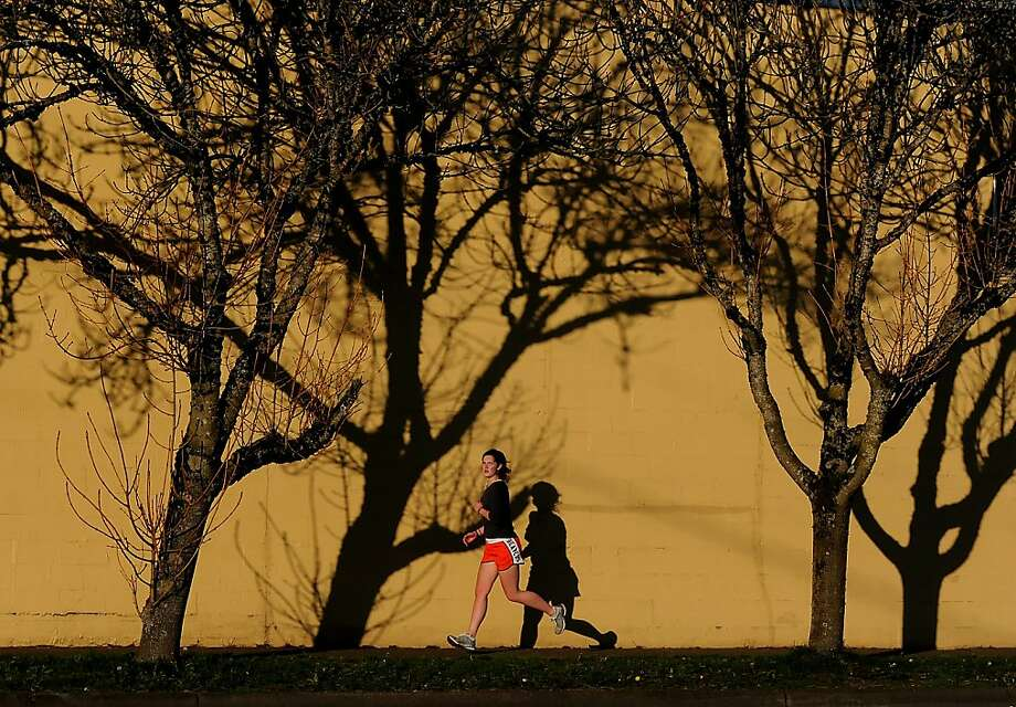 Afternoon sun casts shadows of barren trees as Oregon State University sophomore Sophia Cotgrove enjoys the nice weather during a workout near the intersection of Southwest Fifth Street and Southwest Western Boulevard on Friday Feb. 15, 2013 in Corvallis, Ore. Residents were treated to another day of blue skies and sunshine during a break from the winter weather. Photo: Amanda Cowan, Associated Press