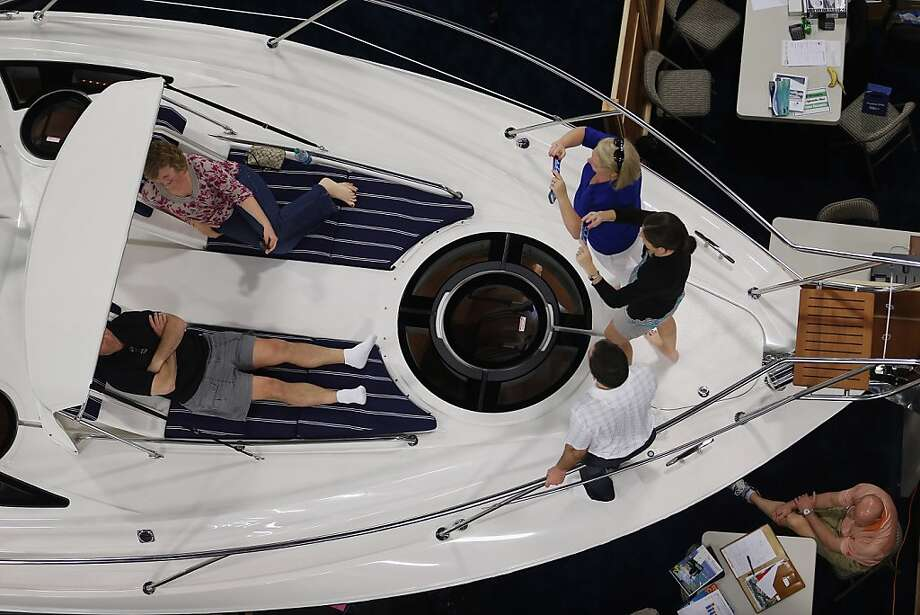 People look at boats on display at The Miami International Boat Show at the Miami Beach Convention Center on February 15, 2013 in Miami Beach, Florida. The boat show has more than 3,000 boats on display and more than 1,000 boating accessories, the show ends on Monday. Photo: Joe Raedle, Getty Images