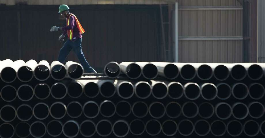 A Tenaris employee lines up a stack of pipes so a forklift can pick it up. The piping made in Matagorda County will be used in shale drilling operations throughout the United States. Photo: Houston Chronicle Photos