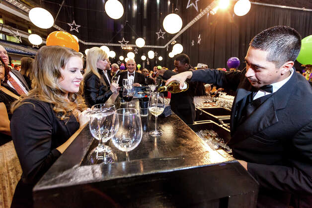Bartender Hectory Ybarra pours a glass of wine for Tara Barisic during the San Antonio Sports Hall of Fame Class of 2013 induction ceremony at the Alamodome on Friday, Feb. 15, 2013.  MARVIN PFEIFFER/ mpfeiffer@express-news.net Photo: MARVIN PFEIFFER, Marvin Pfeiffer/ Express-News / Express-News 2013