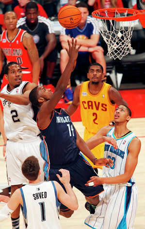 Team Shaq's Michael Kidd-Gilchrist (center) shoots between Team Chuck's Kawhi Leonard, Team Chuck's Alexey Shved, and Team Chuck's Anthony Davis during second half action of the BBVA Rising Stars Challenge at the Toyota Center Friday Feb. 15, 2013 in Houston, Texas. Team Chuck won 163-135. Photo: Edward A. Ornelas, San Antonio Express-News / © 2013 San Antonio Express-News