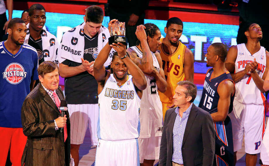 TNT's Craig Sager (left) and BBVA President and COO Angel Cano (right) look on as Team Chuck's Kenneth Faried (center) holds the game MVP Trophy after the BBVA Rising Stars Challenge at the Toyota Center Friday Feb. 15, 2013 in Houston, Texas. Team Chuck won 163-135. Photo: Edward A. Ornelas, San Antonio Express-News / © 2013 San Antonio Express-News