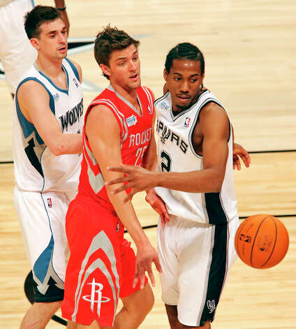 Team Shaq's Chandler Parsons passes around Team Chuck's Kawhi Leonard as Team Chuck's Alexey Shved looks on during second half action of the BBVA Rising Stars Challenge at the Toyota Center Friday Feb. 15, 2013 in Houston, Texas. Team Chuck won 163-135. Photo: Edward A. Ornelas, San Antonio Express-News / © 2013 San Antonio Express-News