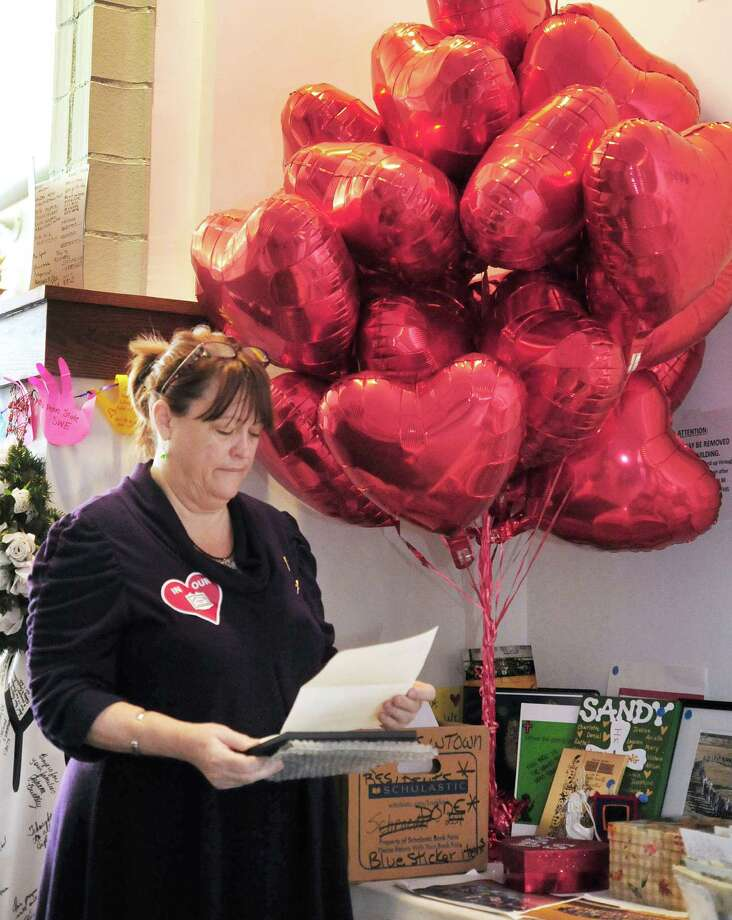 Suzanne Davenport, of Sandy Hook, reads one of the many outpourings of sympathy for the tragedy at Sandy Hook Elementry School collected at Town Hall, Newtown, Conn. Saturday, Feb. 16, 2013. Saturday is the last day of public viewing before the objects are catalogued and stored away. Photo: Michael Duffy / The News-Times