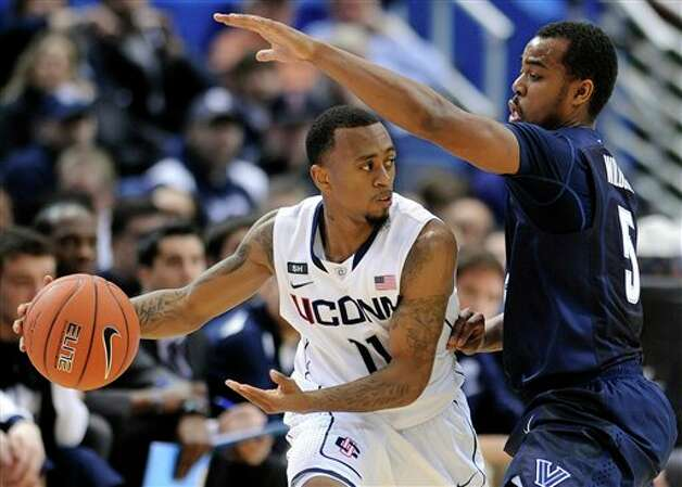 Connecticut's Ryan Boatright, left, is guarded by Villanova's Tony Chennault during the first half of an NCAA college basketball game in Hartford, Conn., Saturday, Feb. 16, 2013. (AP Photo/Fred Beckham)