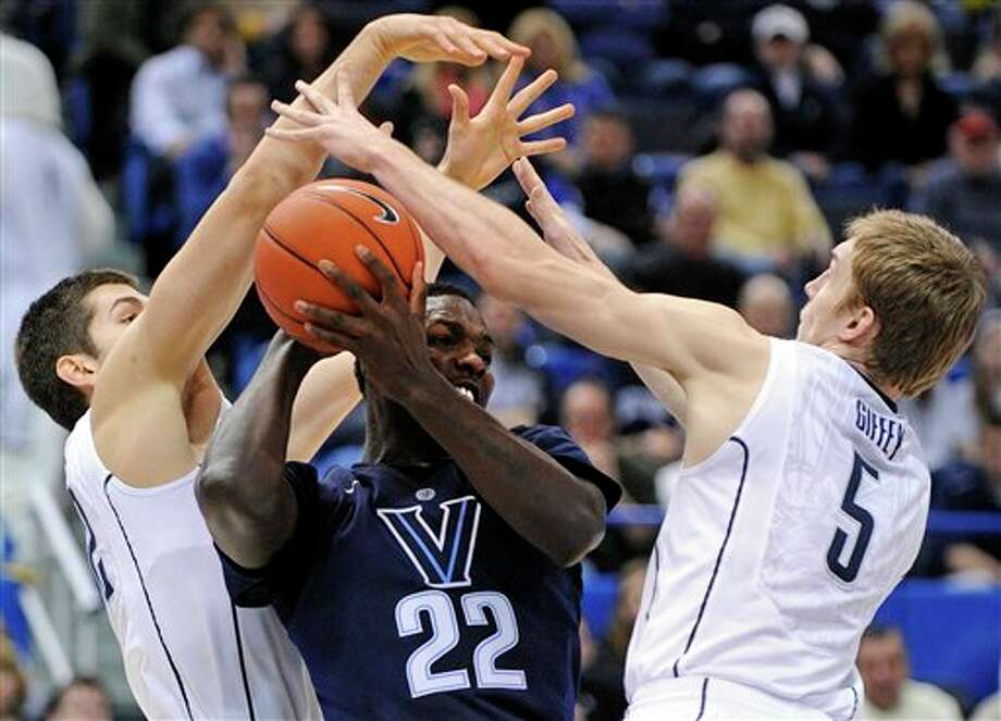 Connecticut's Leon Tolksdorf, left, and Niels Giffey, right, defend Villanova's JayVaughn Pinkston during the first half of an NCAA college basketball game in Hartford, Conn., Saturday, Feb. 16, 2013. (AP Photo/Fred Beckham)