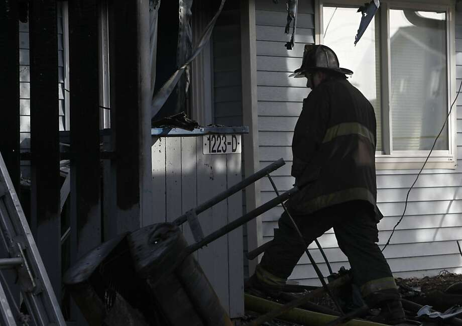 A Firefighter enters a heavily damaged apartment after an overnight fire on Treasure Island killed a 10-year-old girl in San Francisco, Calif. on Saturday, Feb. 16, 2013. Photo: Paul Chinn, The Chronicle