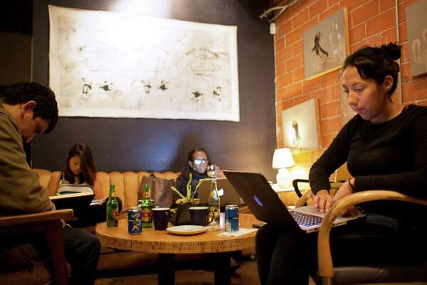 """Jeanine Salinas (right) works at her computer while sitting in Antidote Coffee, Sunday, Nov. 6, 2011, in Houston. """"I find that hard to believe that I'm going to make less money than my parents,"""" Salinas said. """"It's awful thinking about not being able to take care of my family and still enjoy myself."""""""