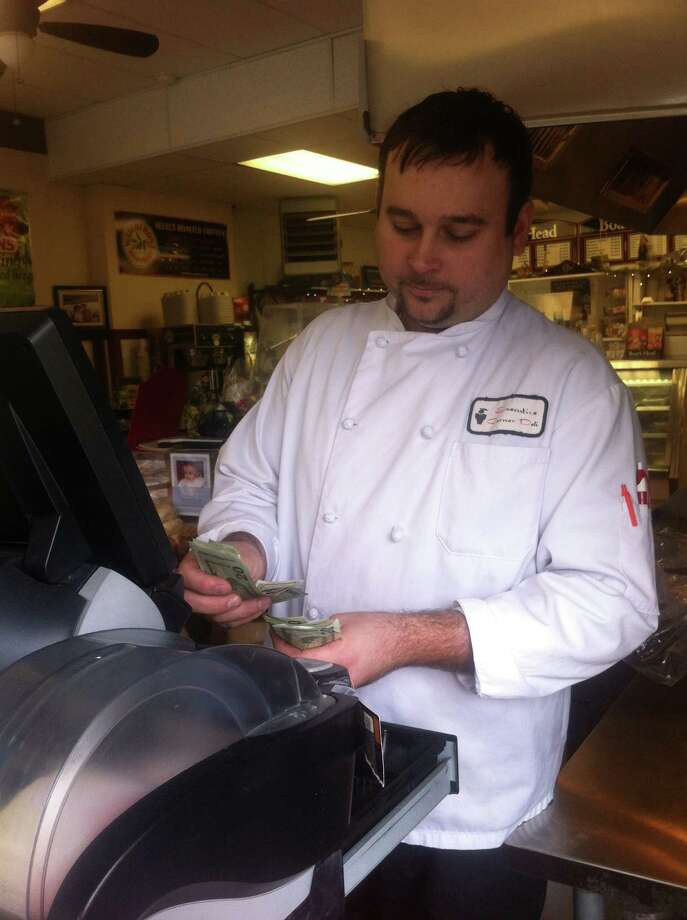 Kevin Allmashy, owner and executive chef of Executive Corner Deli & Catering, behind the register at the Byram store Saturday, Feb. 16, 2013. A man passed a counterfeit $100 bill to a store employee the afternoon of Feb. 13, Allmashy said. Photo: David Hennessey / Greenwich Time