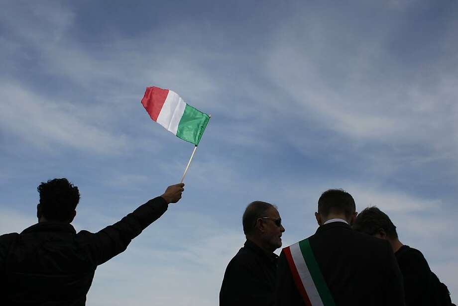 Fans gather at Pier 39 and wave Italian flags to greet the arrival of the Maserati on Saturday, Feb. 16. The yacht broke a world record by sailing around the Cape Horn from New York to San Francisco in 47 days. Photo: James Tensuan, The Chronicle
