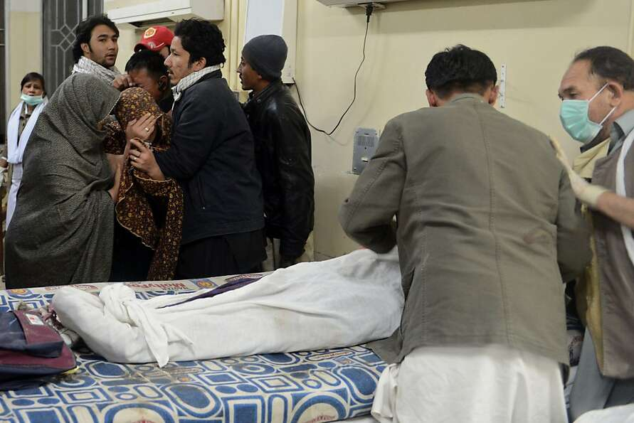 Pakistani Shiite Muslims (left) mourn the death of relatives killed in a bomb blast, at a hospital i