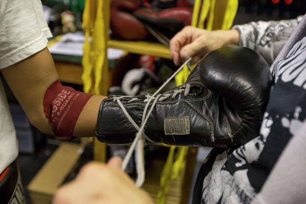 Sam Randazzo, right, helps Adrian Rodriguez, 14, with his boxing gloves at the Randazzo Bros. Boxing Gym, the only such facility on the northeast side, on Thursday, Feb. 14, 2013. Photo: Michael Miller, For The Express-News / For the Express-News