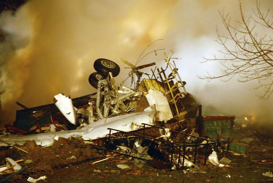 FILE - In this Feb. 12, 2009, file photo, the wreckage of Continental flight 3407 lies amid smoke at the scene after crashing into a suburban Buffalo home and erupting into flames, killing all 48 people aboard and at least one person on the ground, according to authorities. Faced with substantial industry opposition, federal regulators are struggling to implement a sweeping aviation safety law enacted in the wake of the last fatal U.S. airline crash nearly four years ago, according to a report by a government watchdog. The Federal Aviation Administration is experiencing lengthy delays in putting in place rules required by the law to increase the amount of experience necessary to be an airline pilot, provide more realistic pilot training and create a program where experienced captains mentor less experienced first officers, according to the report by the Department of Transportation's Inspector General. (AP Photo/Dave Sherman, File) Photo: Dave Sherman, Associated Press
