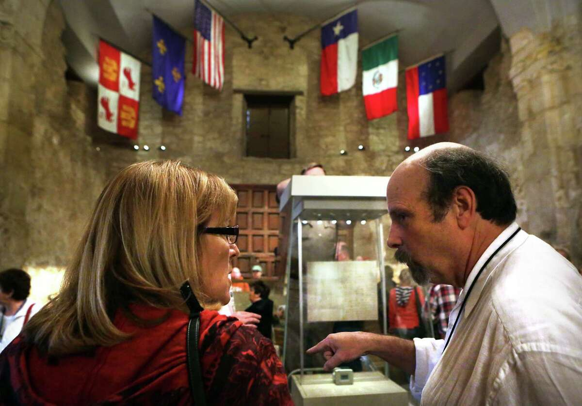 Bruce Winders, right, Curator and Historian at the Alamo, explains to Deb Johnson of Iowa, that the historical Travis Letter will be on display in the case, center, from Feb. 23-March 7. Mark Lambert, Deputy Commissioner of Archives and Records with the Texas General Land Office, made adjustment to and tested the locked and sealed case that will be home to the Travis Letter, on Tuesday, Feb. 12, 2013, at the Alamo.