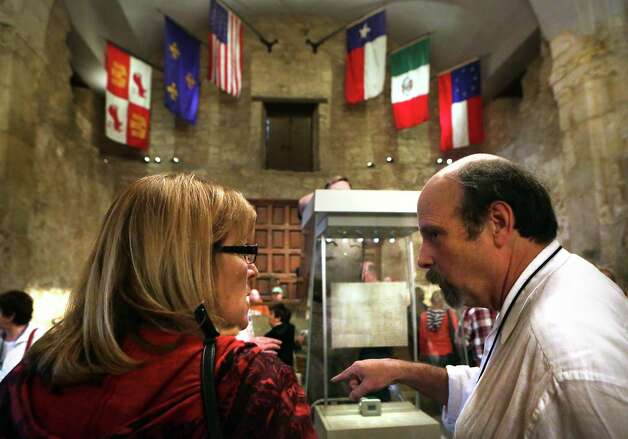 Bruce Winders, right, Curator and Historian at the Alamo, explains to Deb Johnson of Iowa, that the historical Travis Letter will be on display in the case, center, from Feb. 23-March 7.  Mark Lambert, Deputy Commissioner of Archives and Records with the Texas General Land Office, made adjustment to and tested the locked and sealed case that will be home to the Travis Letter, on Tuesday, Feb. 12, 2013, at the Alamo. Photo: Bob Owen, San Antonio Express-News / © 2012 San Antonio Express-News
