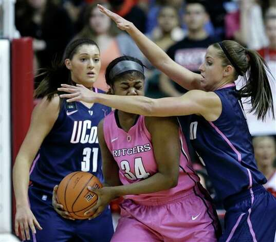 Rutgers' Monique Oliver (34) tries to hold onto the ball as she is defended by Connecticut's Caroline Doty, and Stefanie Dolson (31) during the first half of an NCAA college basketball game Saturday, Feb. 16, 2013, in Piscataway, N.J. (AP Photo/Mel Evans)