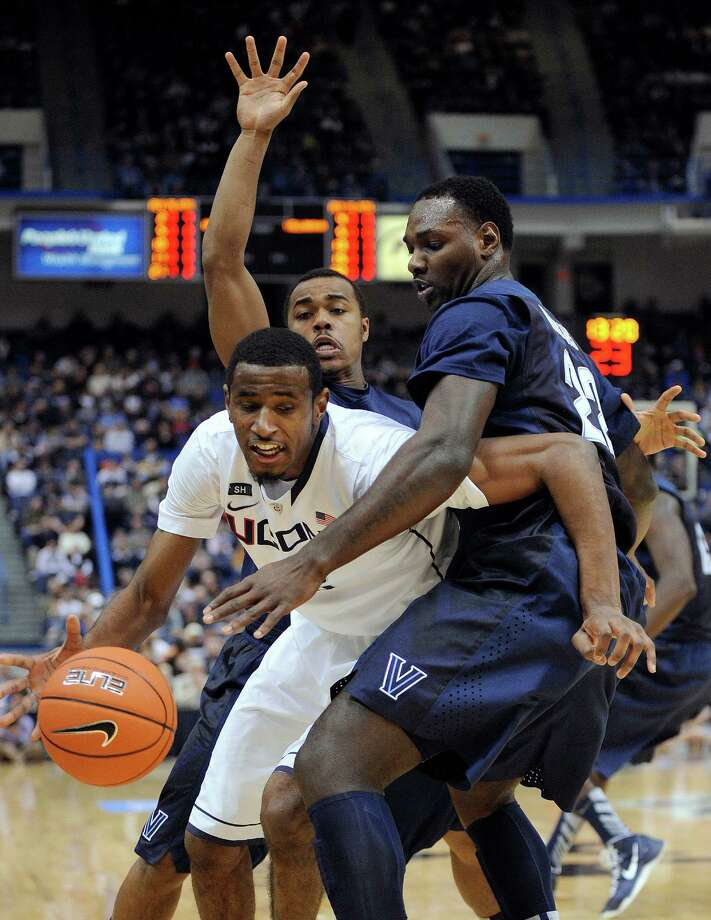 Connecticut's DeAndre Daniels is guarded by Villanova's JayVaughn Pinkston, right, and Tony Chennault during the first half of an NCAA college basketball game in Hartford, Conn., Saturday, Feb. 16, 2013. Villanova won the game 70-61. (AP Photo/Fred Beckham) Photo: Fred Beckham, Associated Press / FR153656 AP