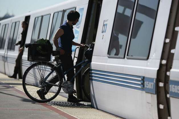Angela Entzel boards a train at BART's MacArthur Station in Oakland. BART is experimenting with allowing more bicycles. Photo: Jessica Olthof, The Chronicle