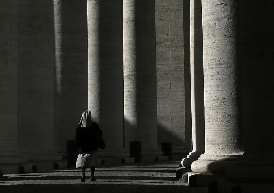 A nun walks under the Bernini colonnade in St. Peter's Square at the Vatican, Friday, Feb. 15, 2013. Pope Benedict XVI signed off on one of the last major appointments of his papacy Friday, approving a German lawyer and financier to head the Vatican's embattled bank. Ernst von Freyberg has solid financial and Catholic credentials as a former investment banker and member of the Sovereign Military Order of Malta, an ancient chivalrous order drawn from European nobility. (AP Photo/Alessandra Tarantino) Photo: Alessandra Tarantino, Associated Press